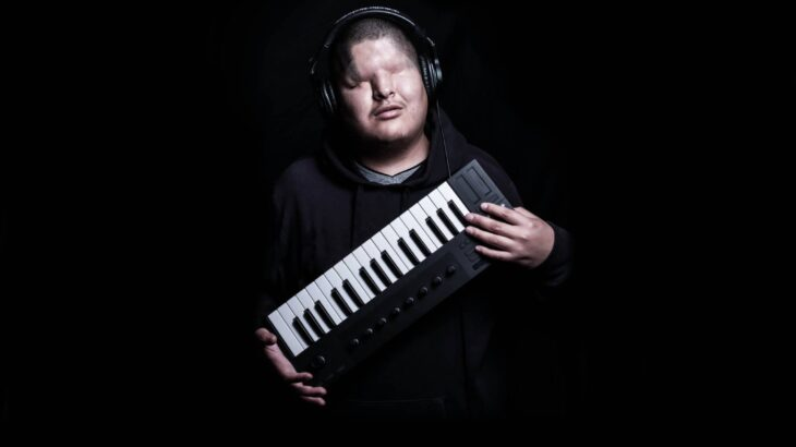 Mattmac stands with headphones on and keyboard in hands with a black background
